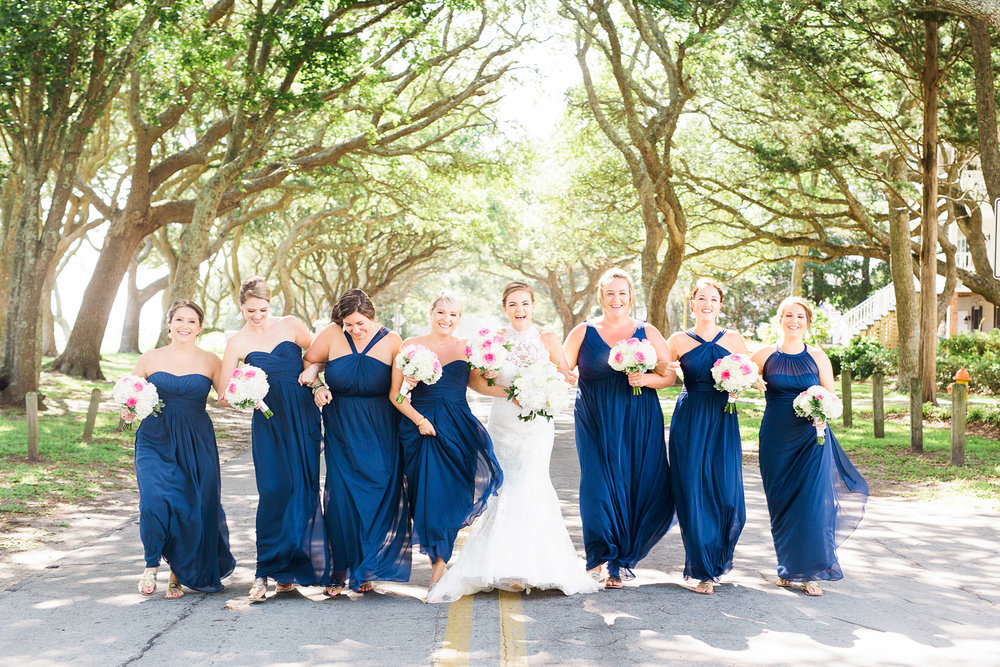 bridal party holds hands and walks down a oak lined road