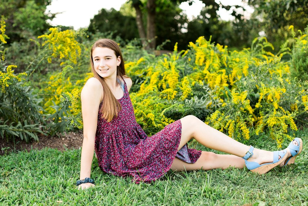 young woman sits in the grass in a field of goldenrod