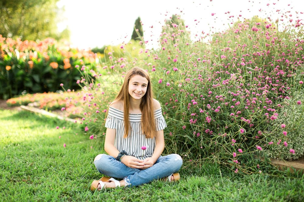 young woman sits cross legged in a garden of purple flowers
