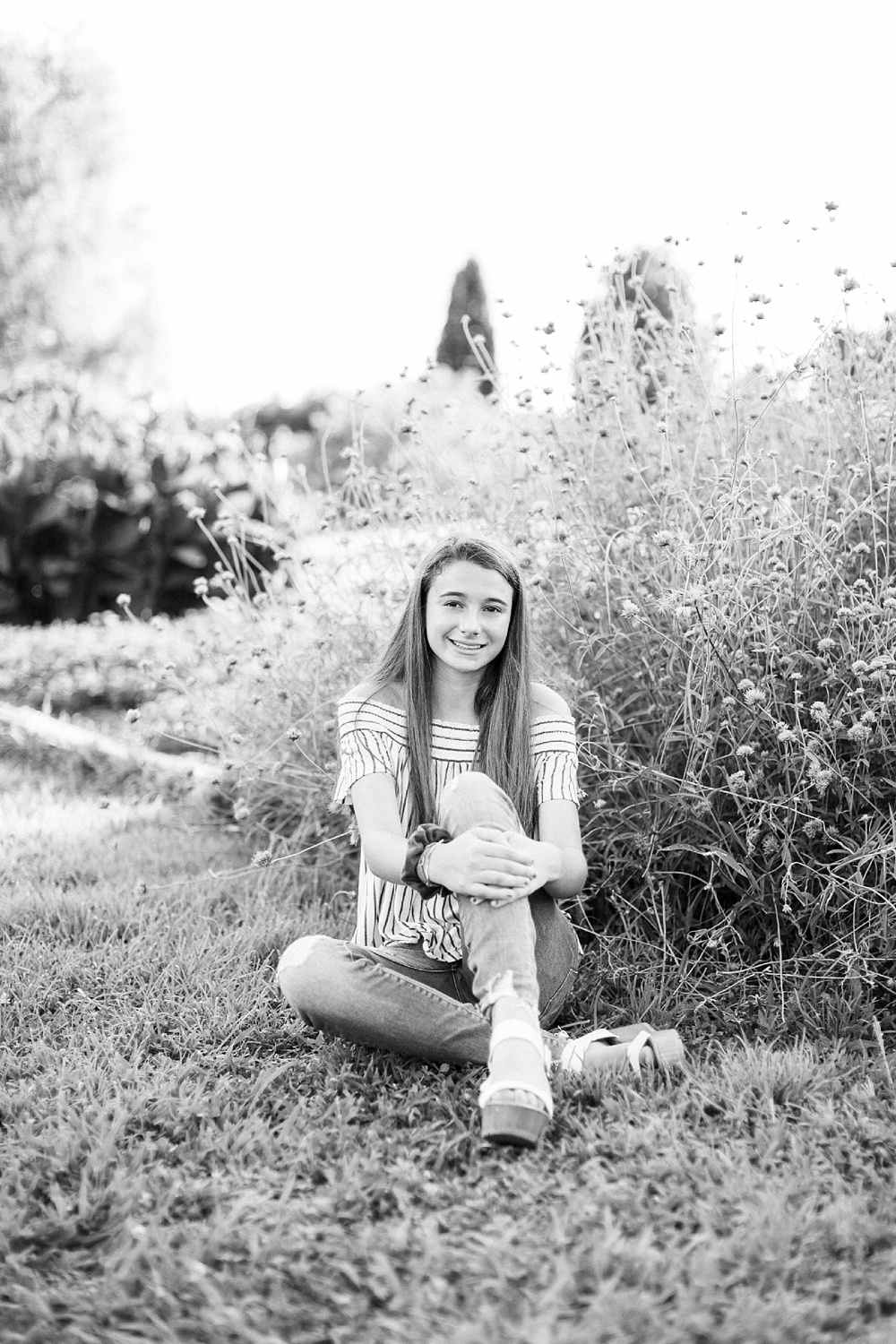 black and white senior portrait of a young woman in a garden