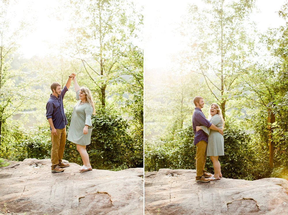 couple dances on a rock outcropping by a lake