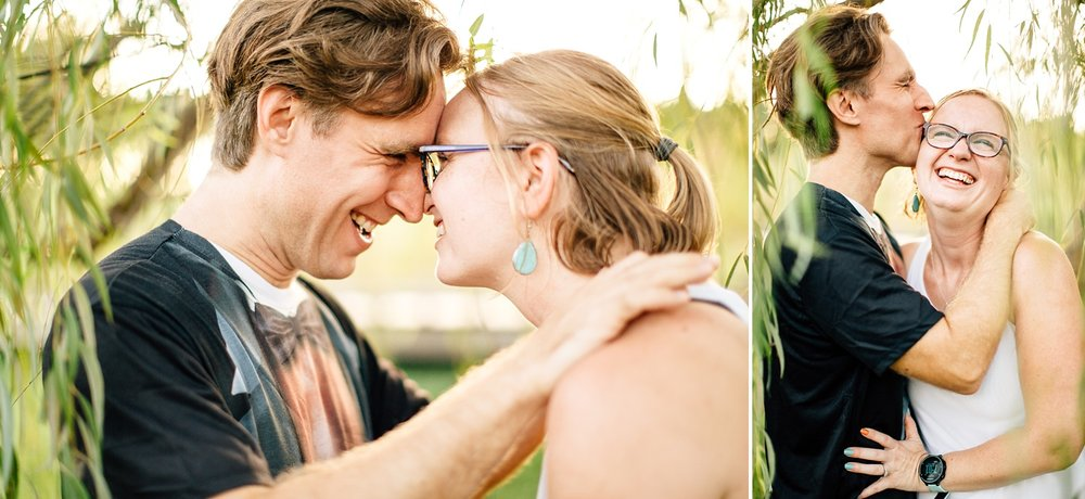 couple smiles and embraces under a willow tree's branches