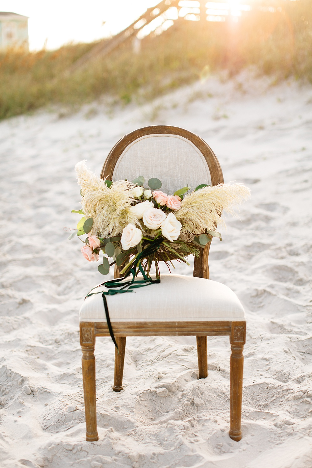bridal bouquet sets on a chair on the beach