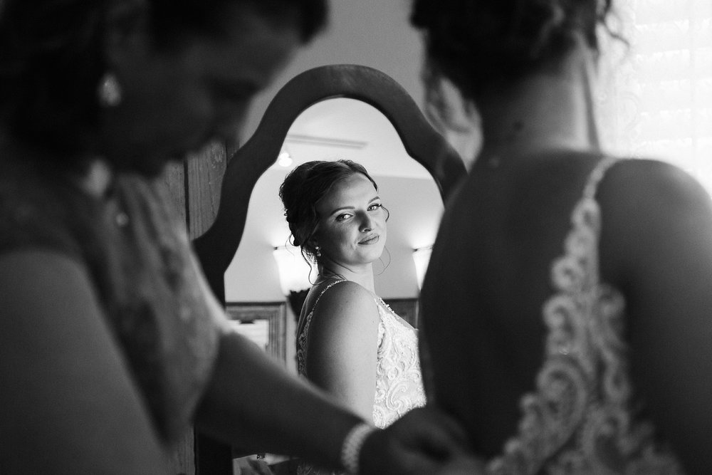 bride smiles in mirror as her mom zips her into her wedding dress