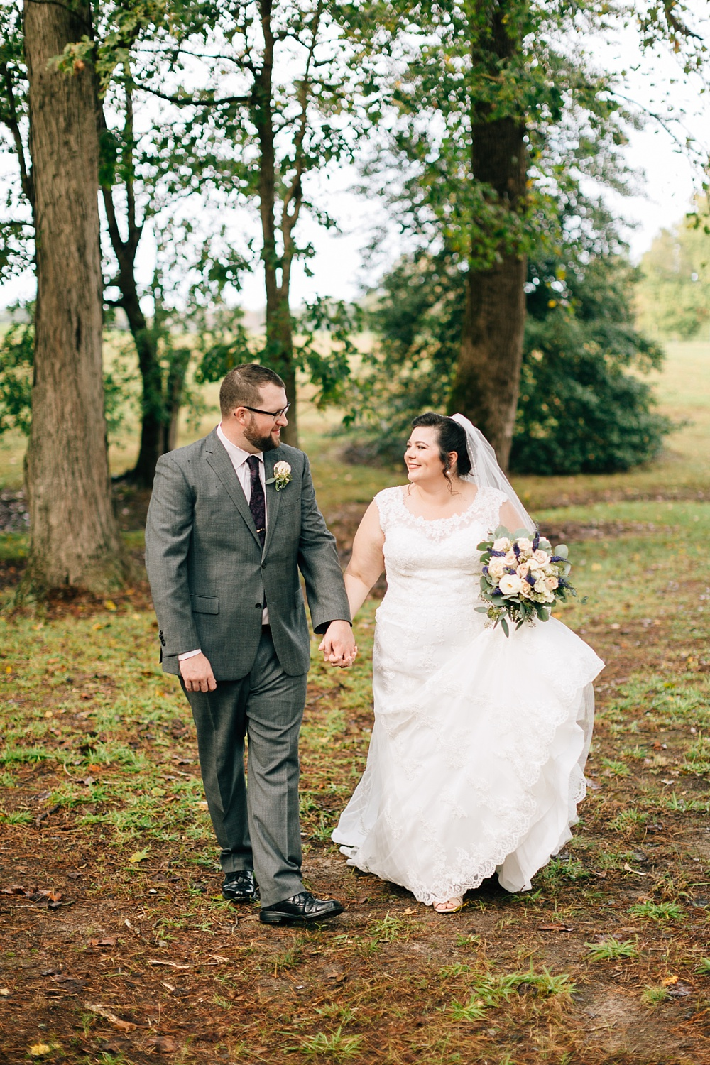 bride and groom walk through the woods and hold hands