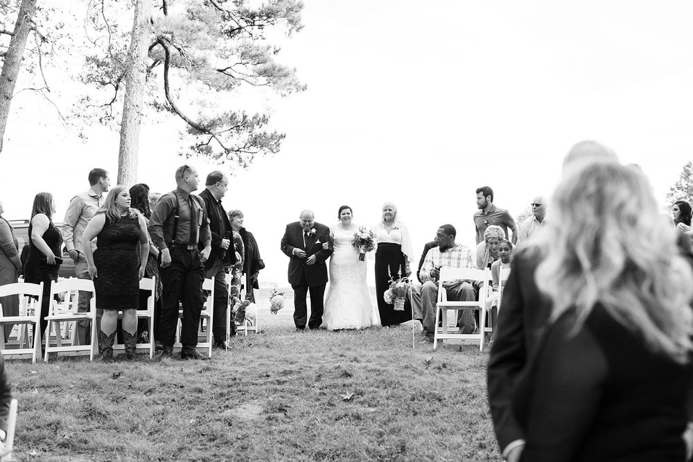 bride walks down the aisle on the arms of her parents