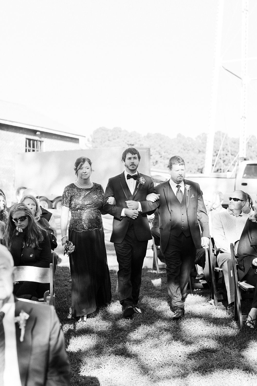 groom walks down the aisle with both of his parents