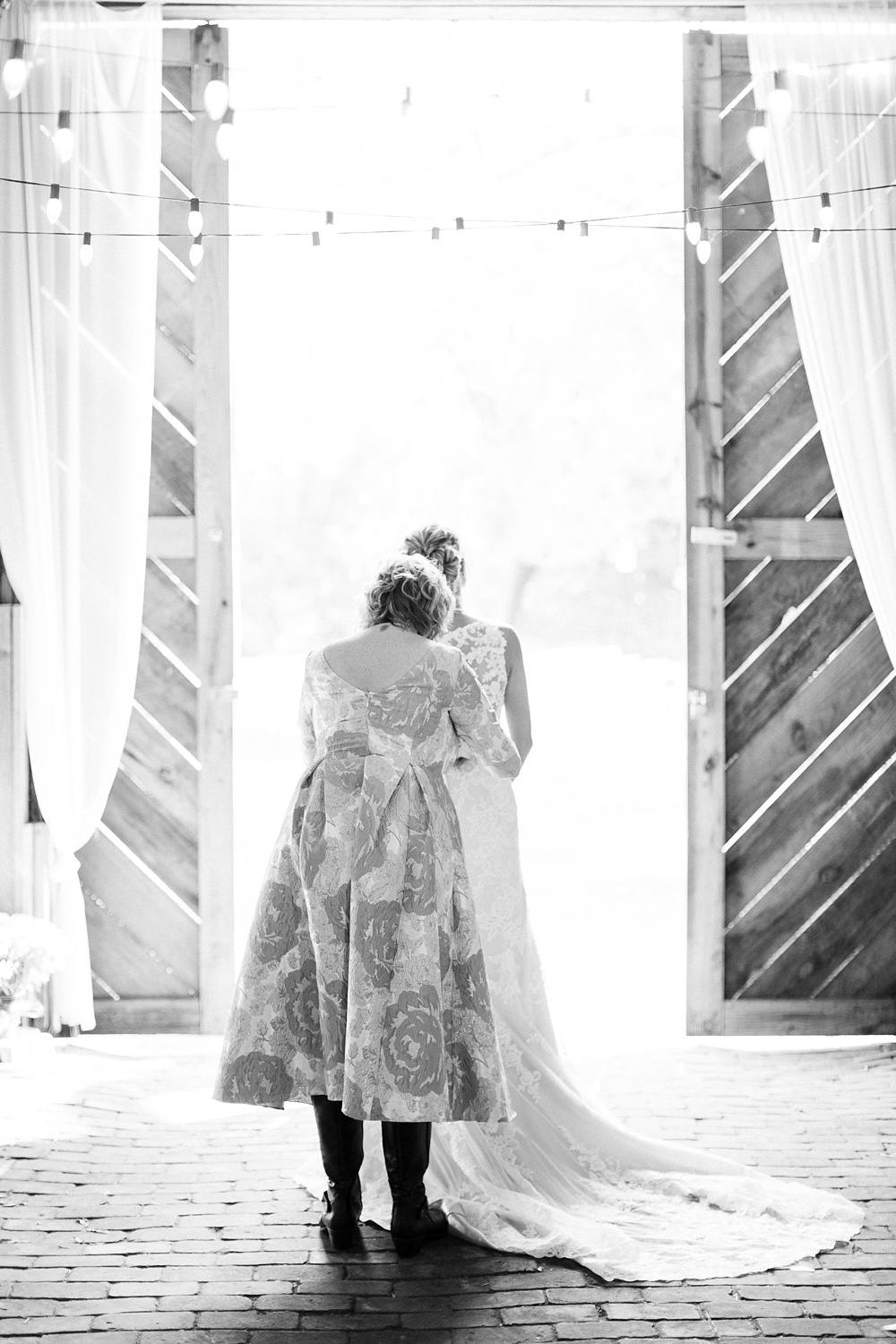 mom helps bride into her wedding gown by rachael bowman photography
