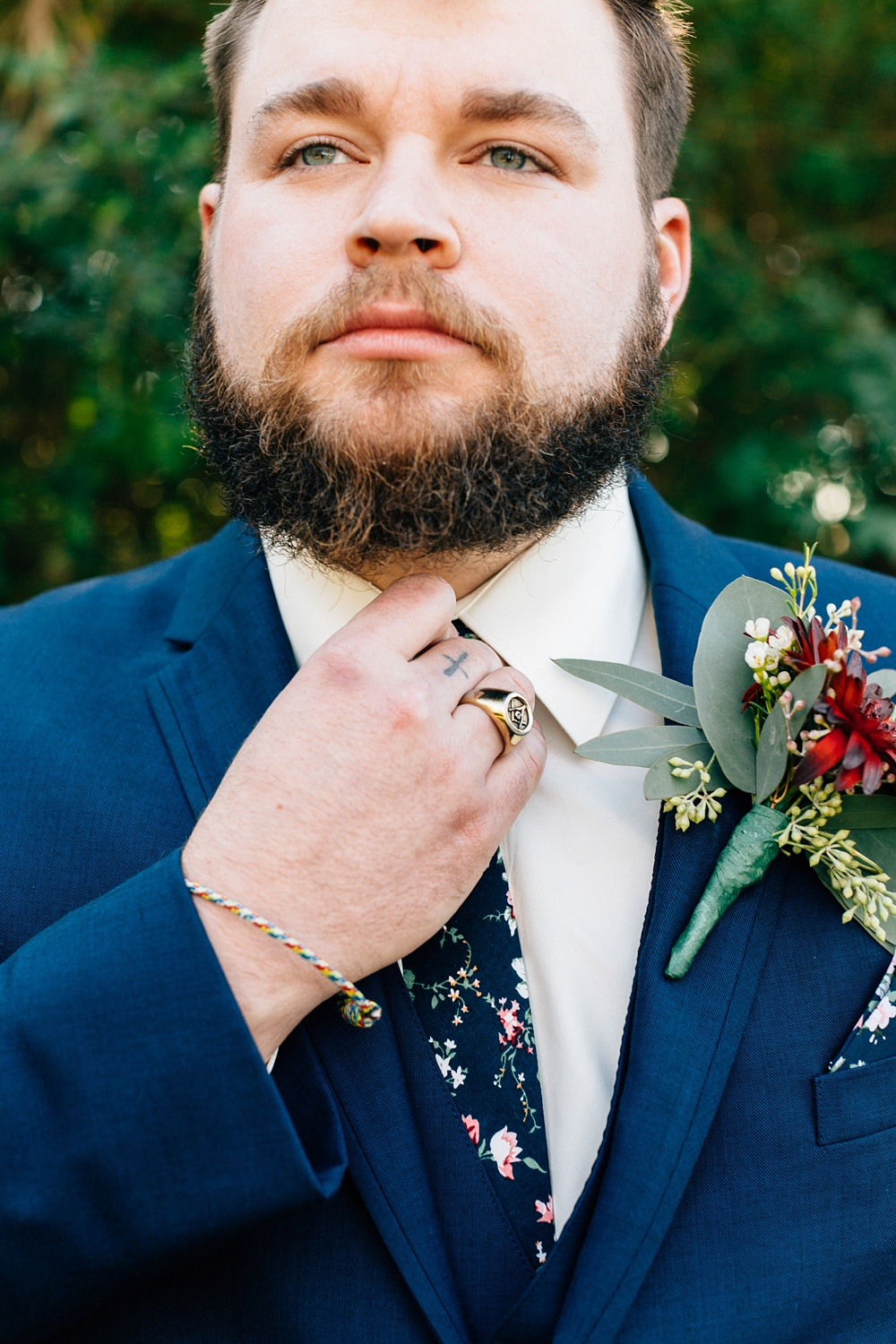 groom straightens his floral tie