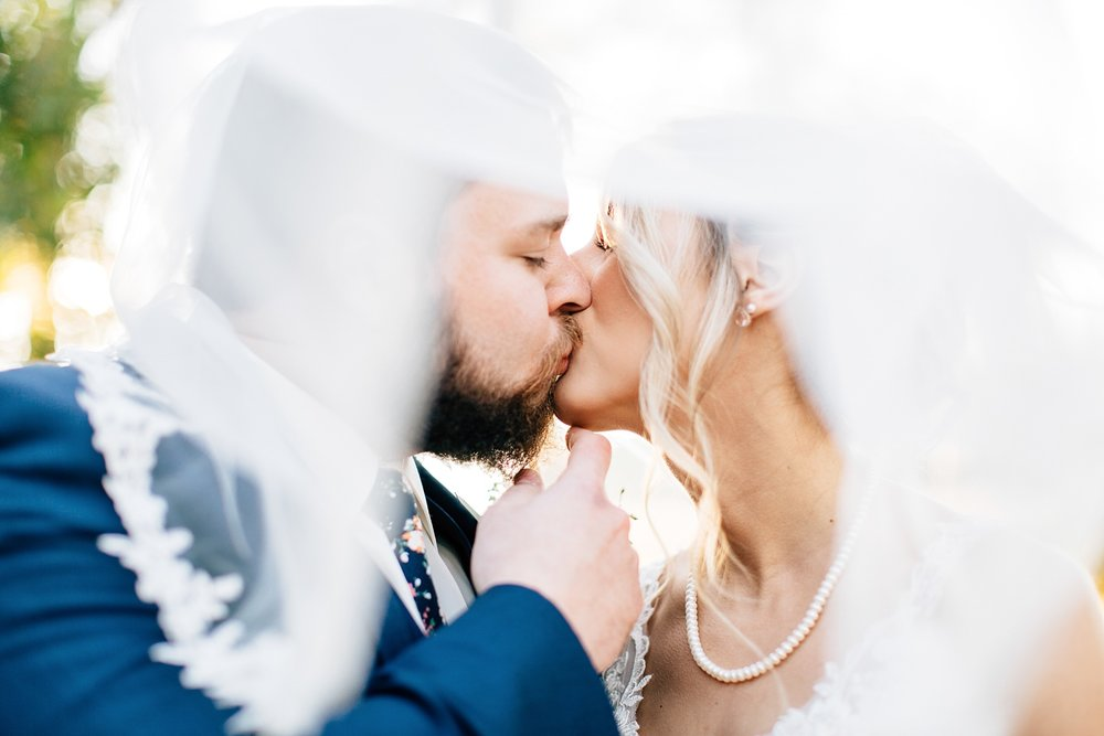 bride and groom kiss under the veil by rachael bowman photography