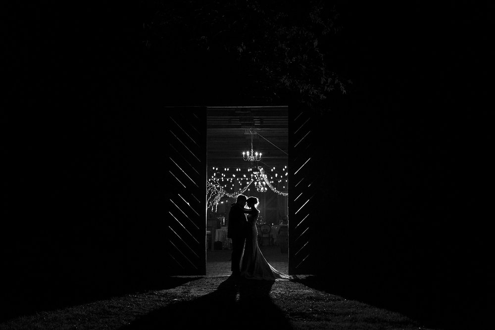 bride and groom in barn door at night by rachael bowman photography