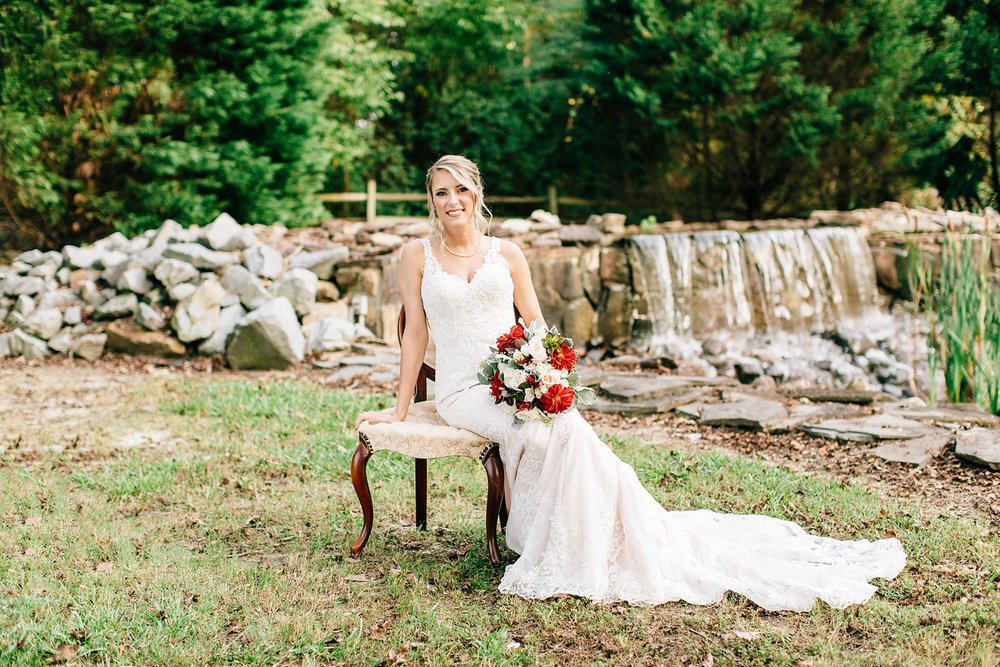 seated bridal portrait in front of a small stone waterfall