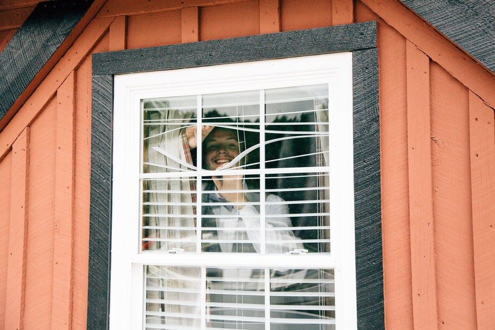 Groom peeking out a window to catch a glimpse of his bride