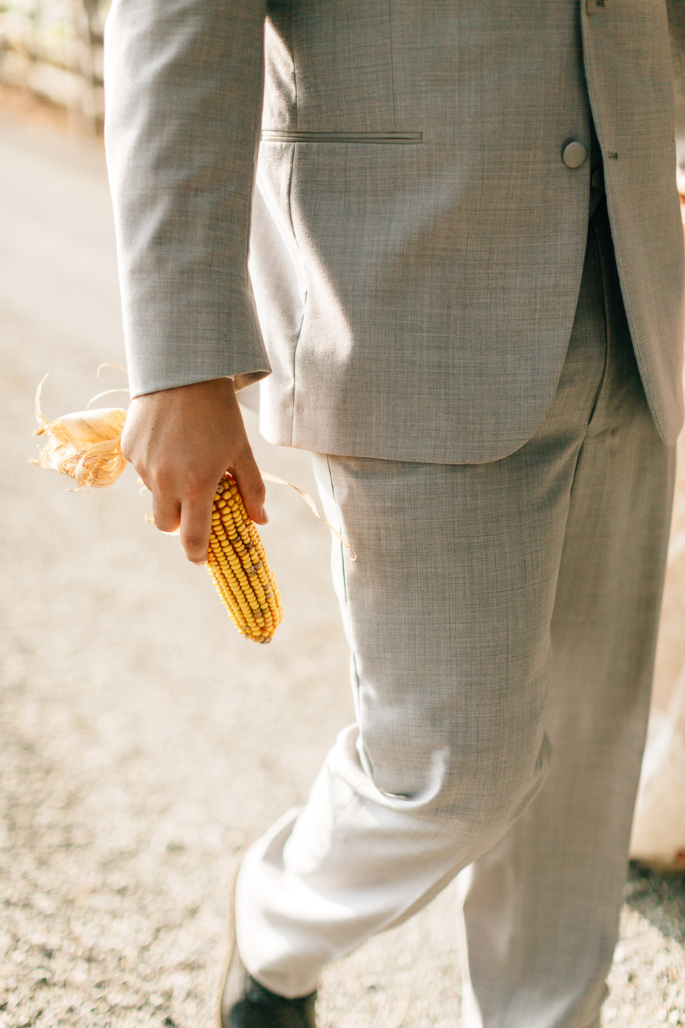 Man in gray suit holding an ear of corn