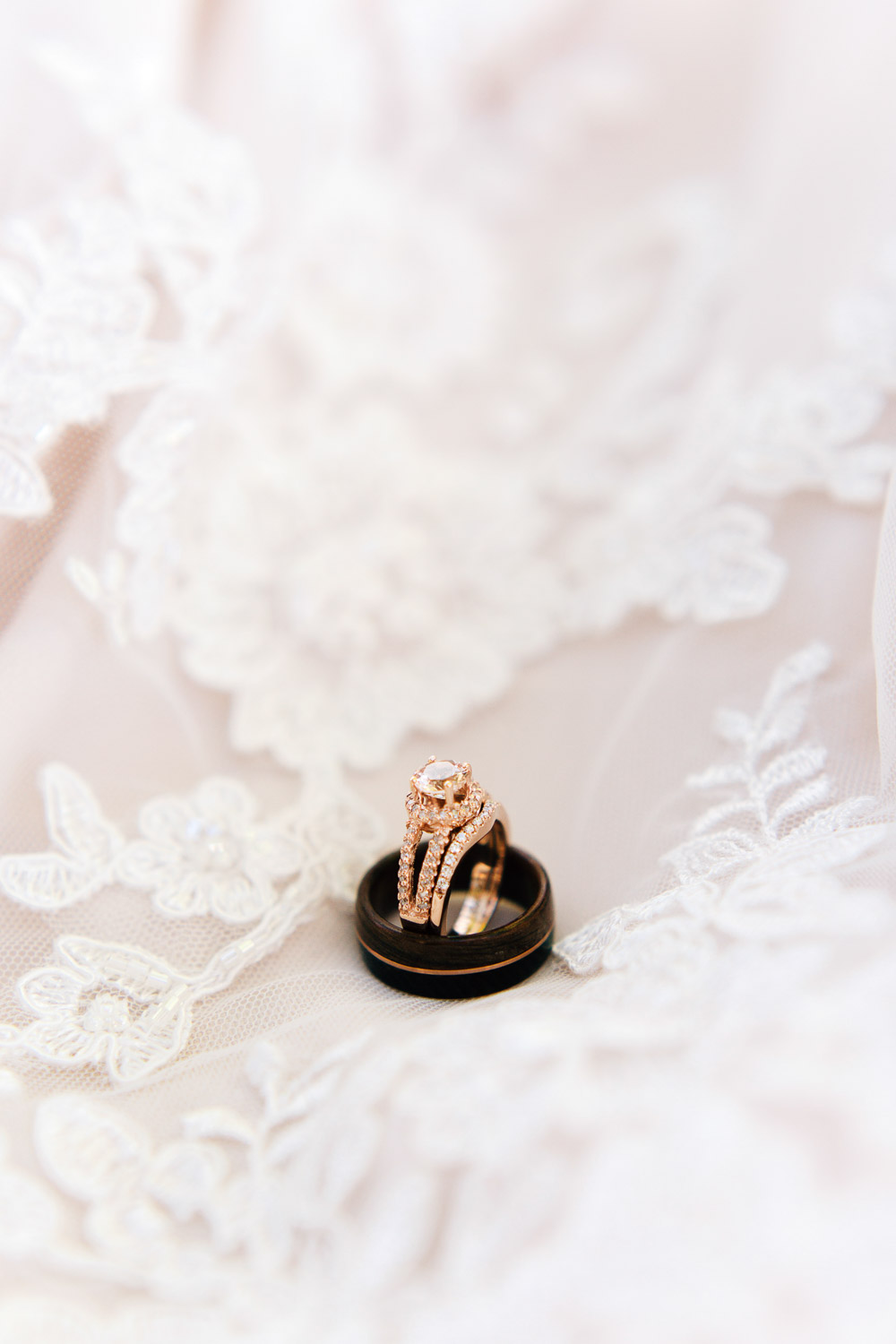 rose gold wedding rings on a lace wedding dress skirt