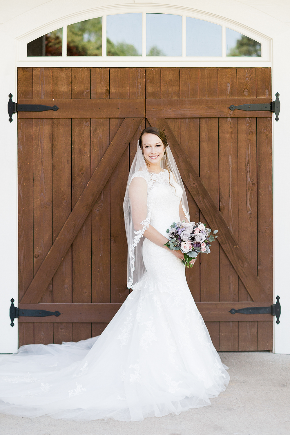 bridal portrait in front of a rustic barn doors