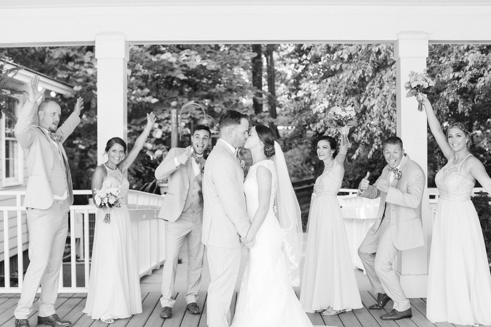wedding party cheers as bride and groom kiss