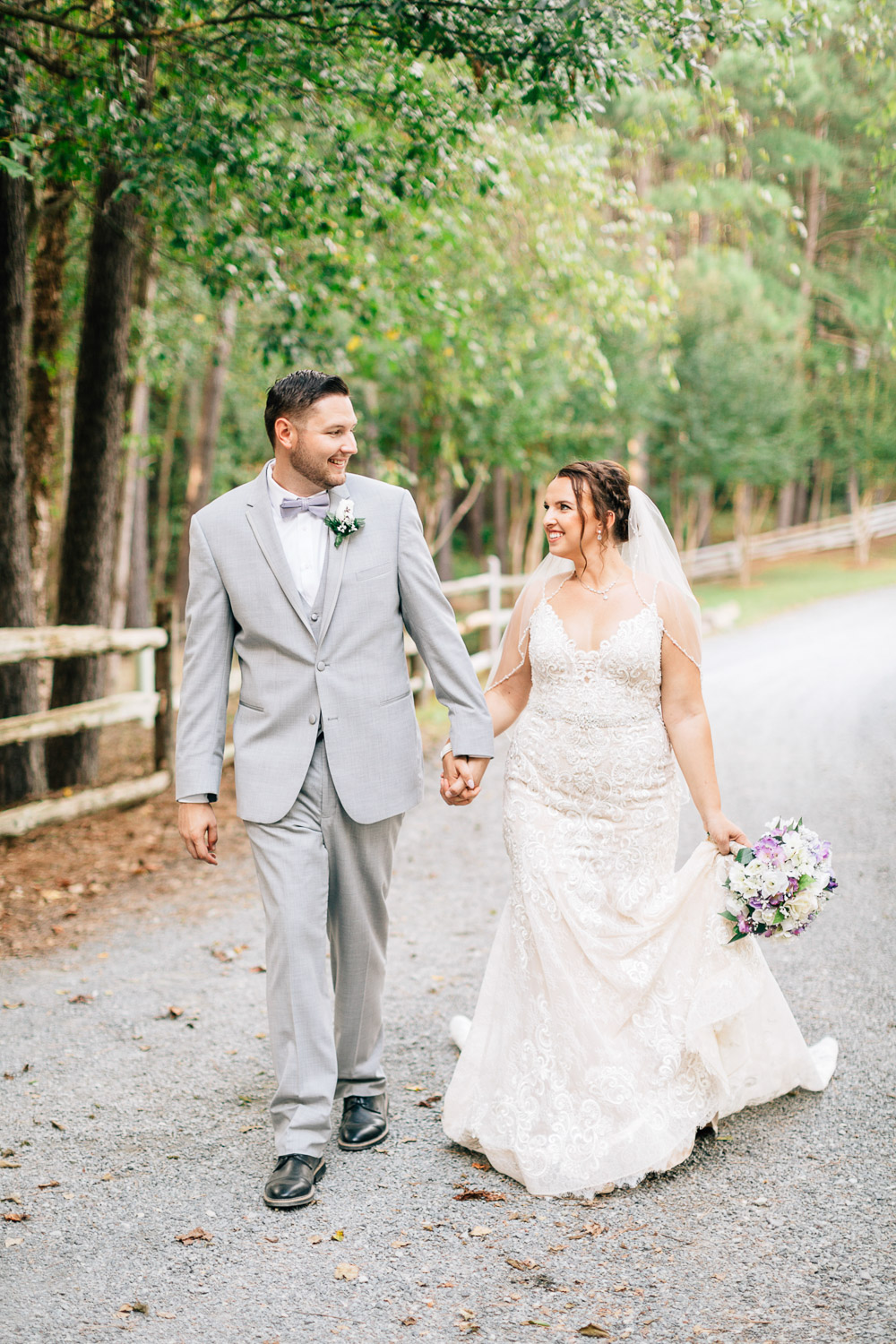 bride and groom walk and hold hands at shady wagon farms