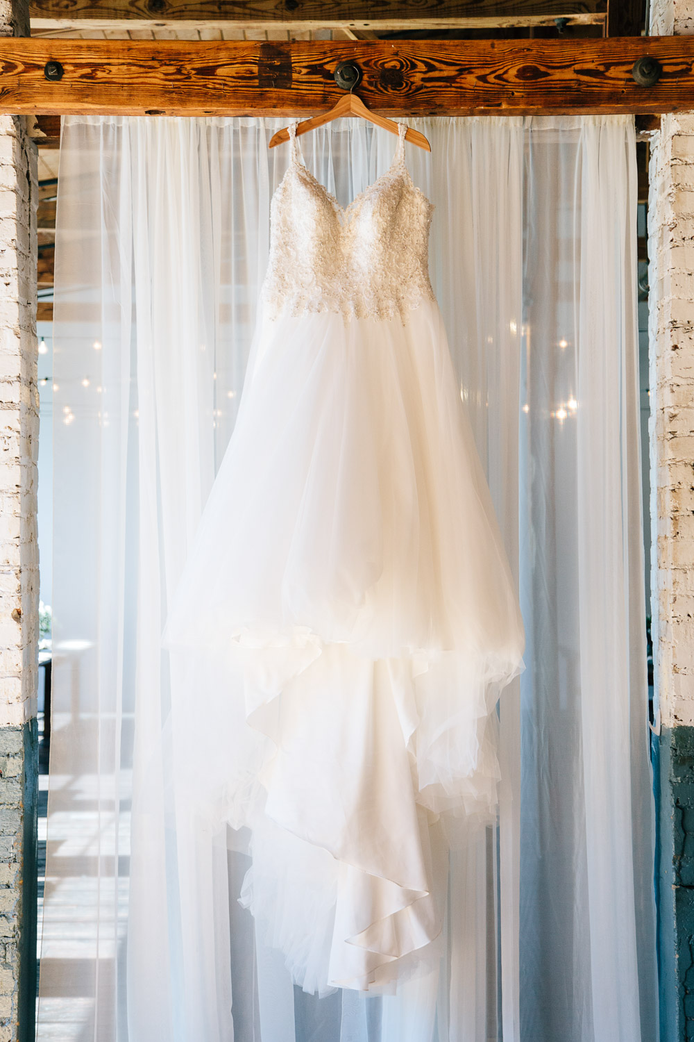 wedding gown hangs from an old wooden beam