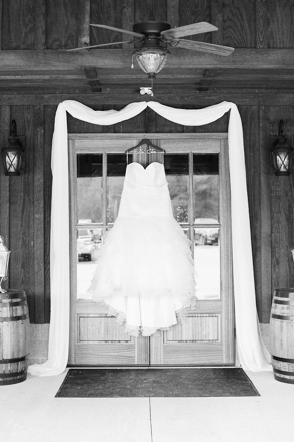 wedding dress hangs from the french doors of the barn at broadslab