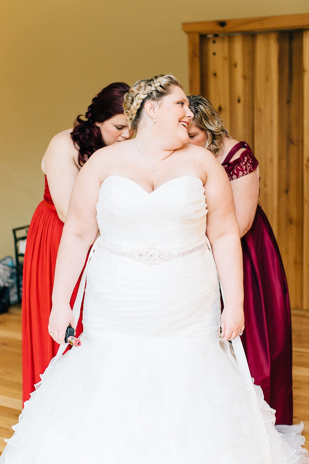 bride gets in her wedding dress with the help of her mother and bridesmaid