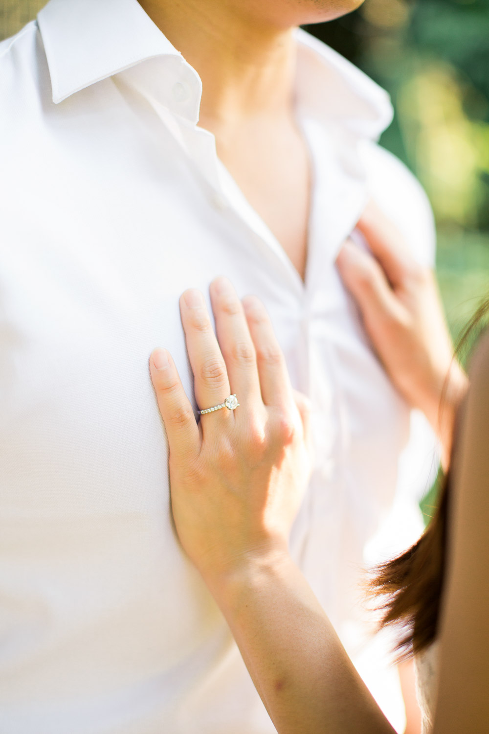 woman's hands rest on her fiance's chest