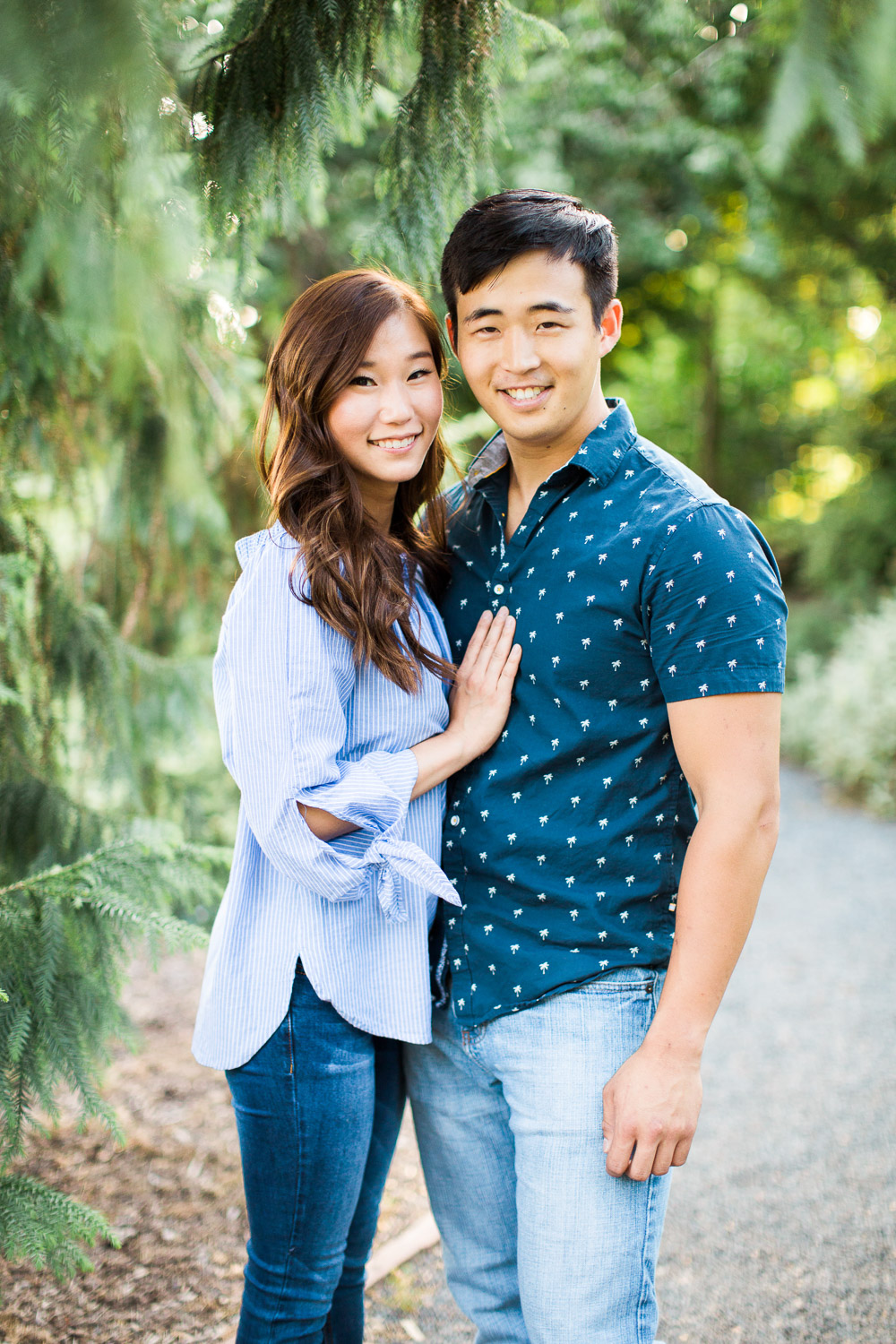 young engaged asian couple stands under a tree