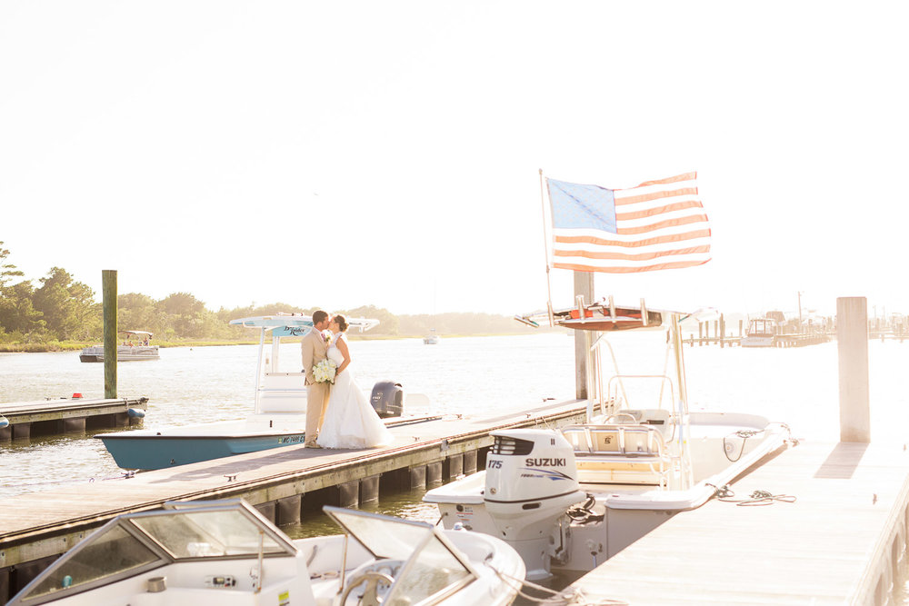 bride and groom kiss on the docks with an american flag in the background