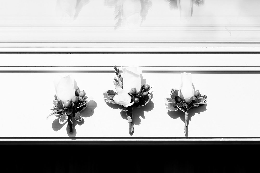 white rose boutonnieres on a window sill