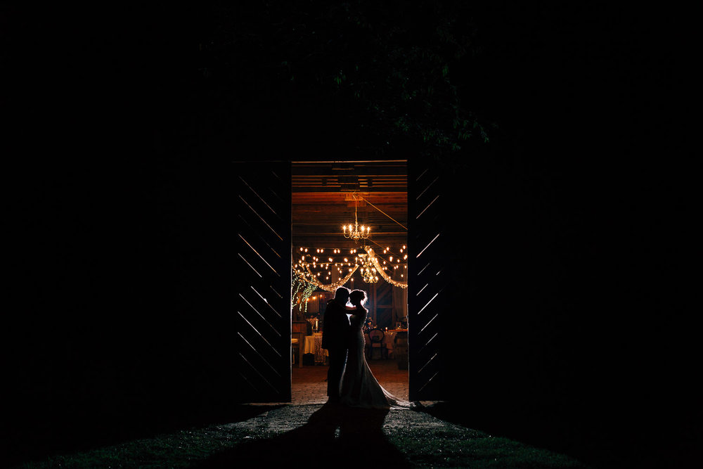 bride and groom at night standing in a barn doorway