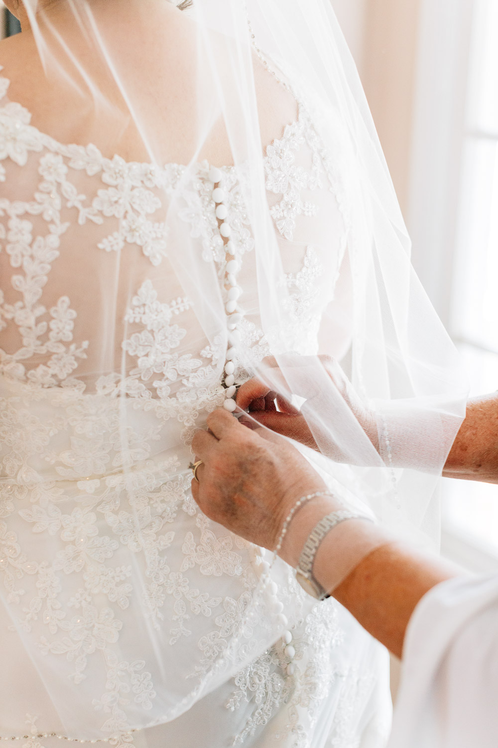 mother buttons daughter into her wedding dress