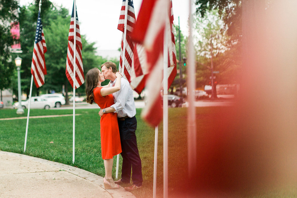 couple kisses surrounded by american flags