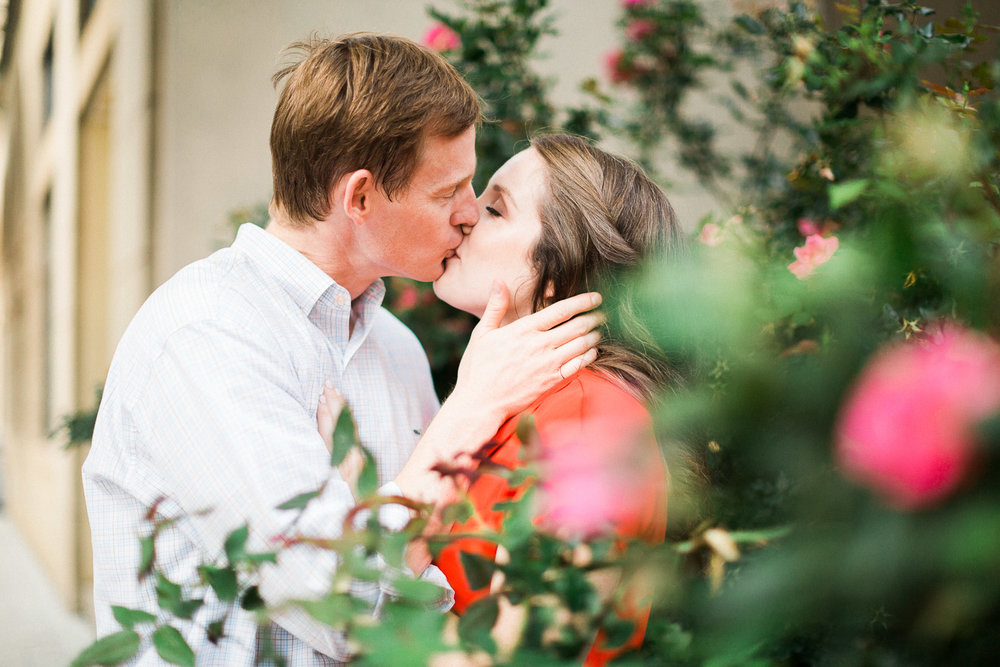 engaged couple kisses in a rose garden