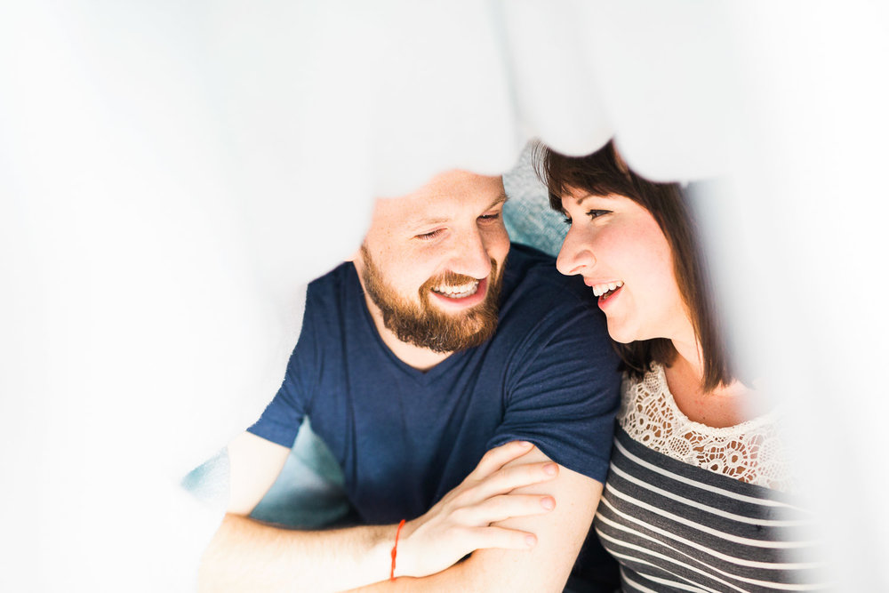 couple laughs under their blanket