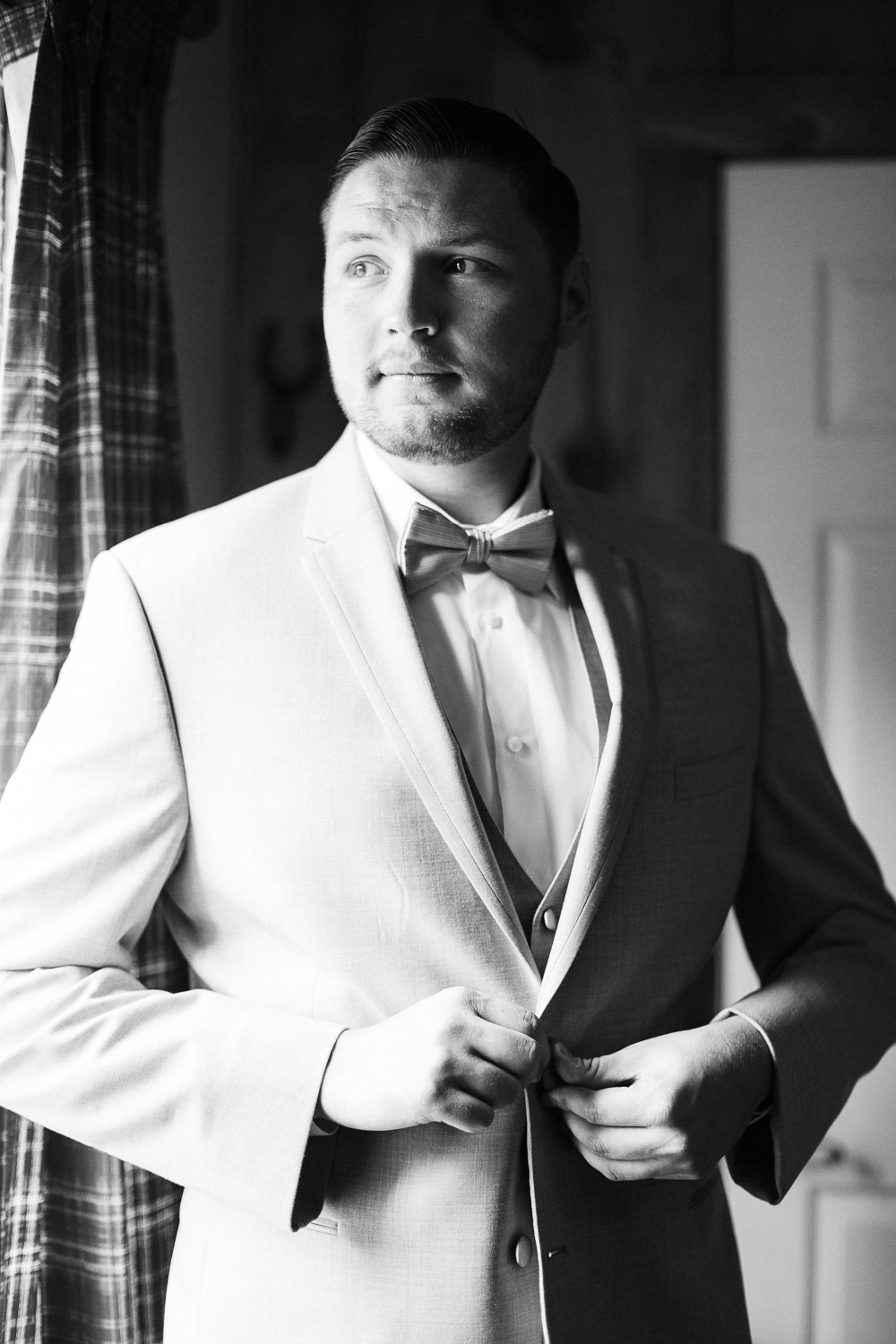 groom buttons jacket and looks out window