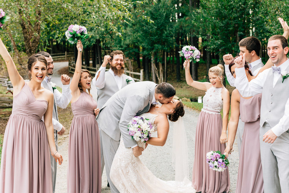 wedding party celebrates as bride and groom kiss