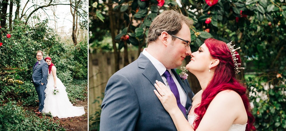 couple snuggles in a secret garden with pink blooms