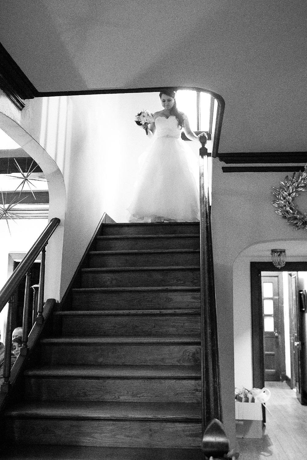 bride comes down stairs to wedding ceremony