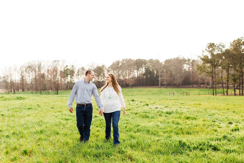 couple walks hand in hand in a sunlit pasture