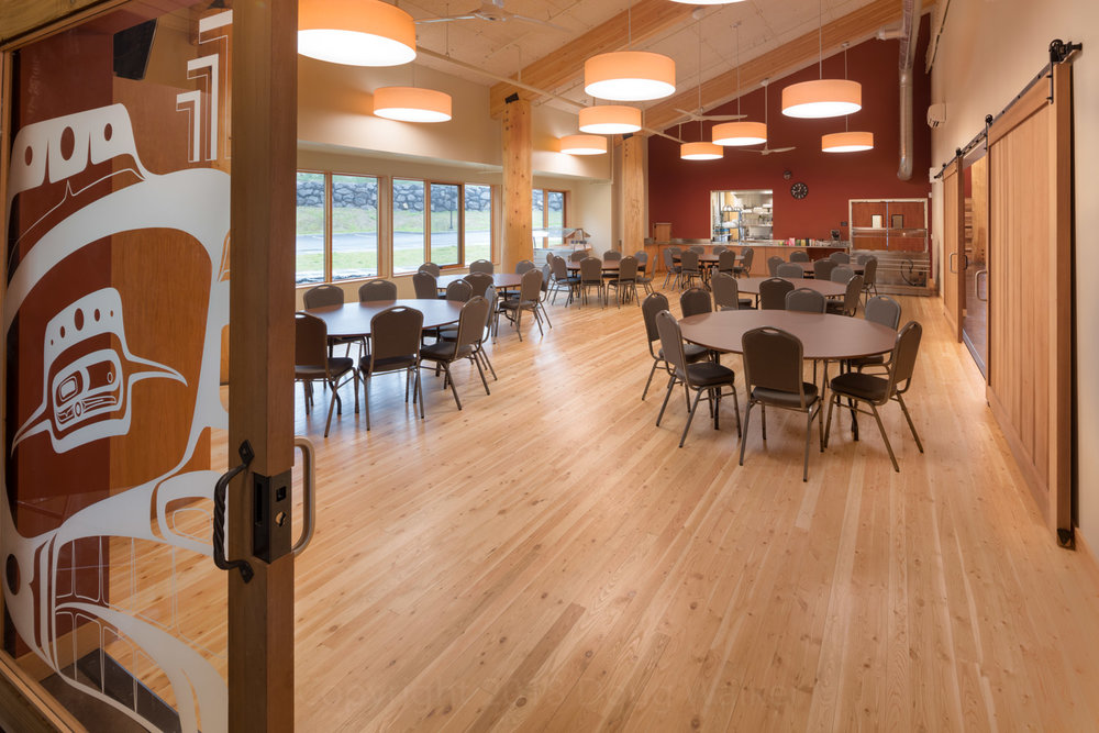 Beautiful glass and cedar doors with Skokomish artwork invite visitors into the Elders Area. Sporting a full kitchen deep space with doors to Gathering Space to the right.