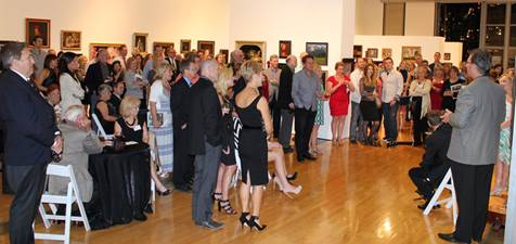 a crowd of people inside a gallery