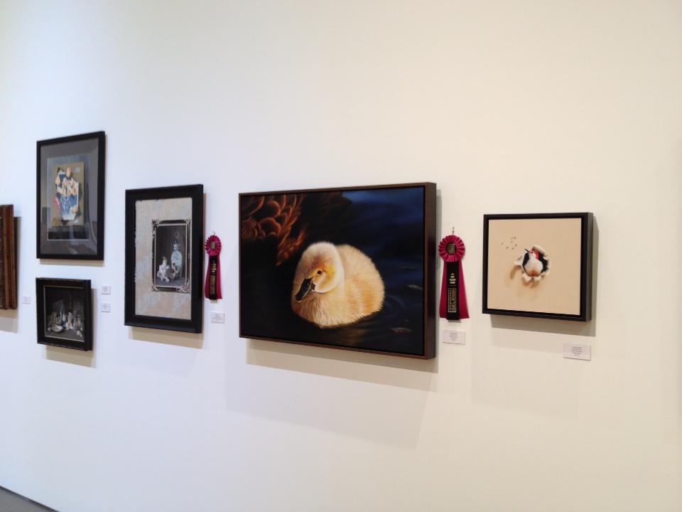 a picture of award winning paintings and 2 magenta ribbons