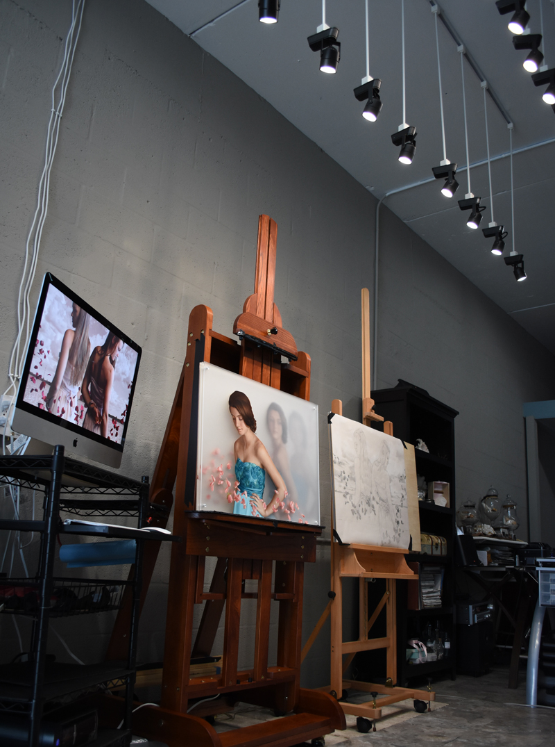 a computer on a cart, two easels and a shelf inside an artist's studio