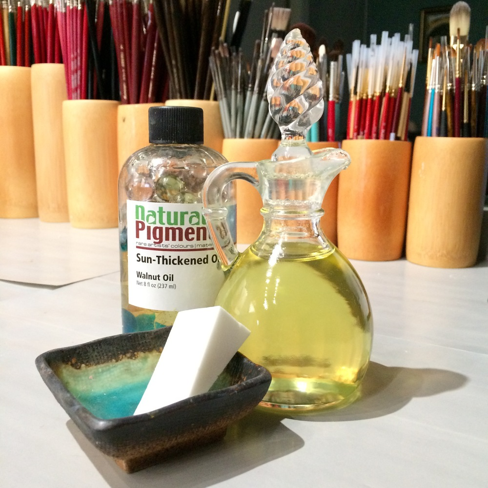 brushes, walnut oil in a bottle and glass jar, cosmetic sponge in a dish.