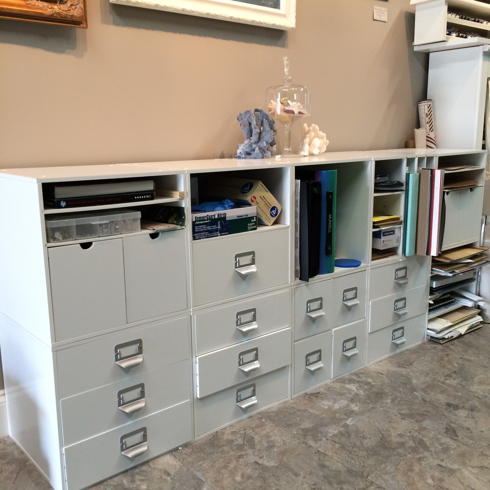 a wall of organizer containers for art supplies