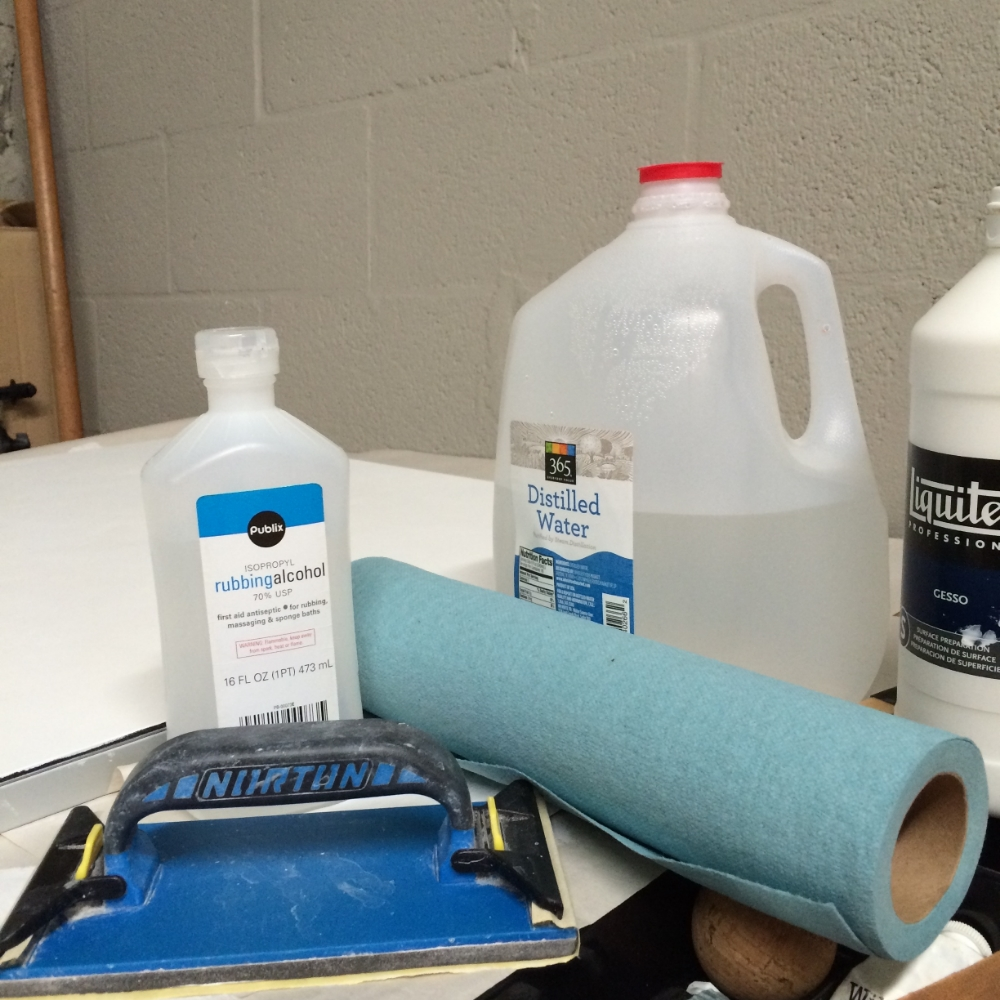 distilled water, rubbing alcohol, sand paper gesso and blue paper towels.