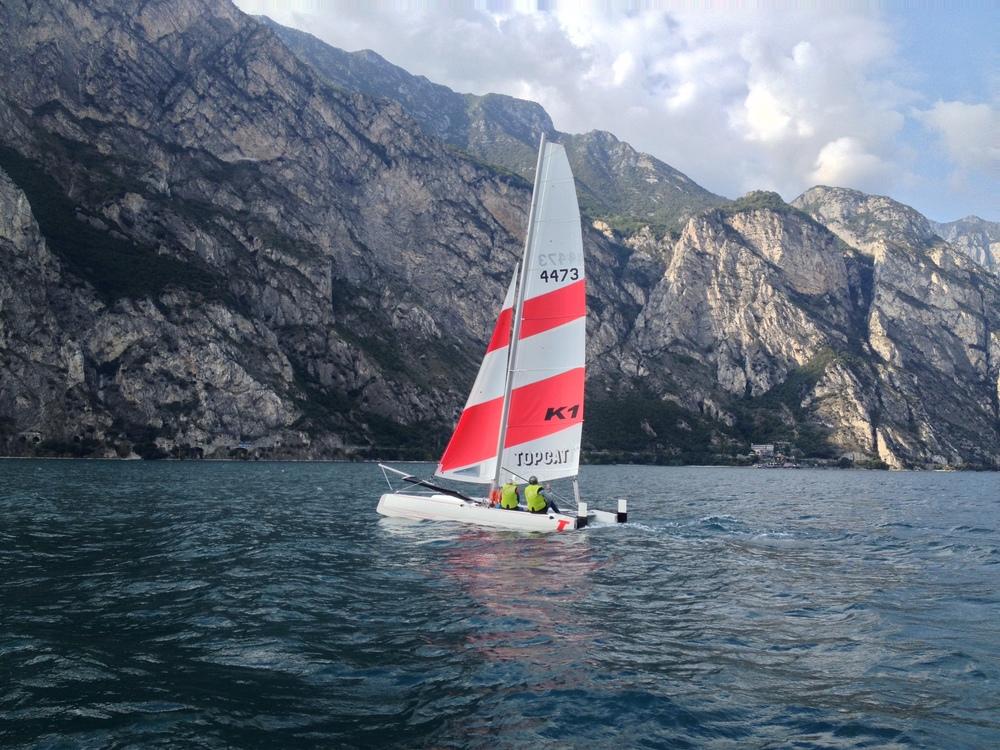 Vader en zoon leren catamaran zeilen op een mooie Oktober middag, instructeur Nic zit in de motor boat en praat in de radio. De studenten met de radiohelmen horen zijn tips en feedback.