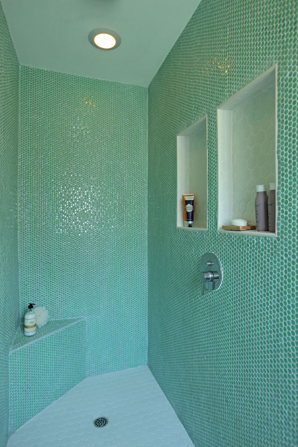 NEED FOR GREEN Floor-to-ceiling jade penny tiles generate vibrancy and life in this gorgeous walk-in shower.