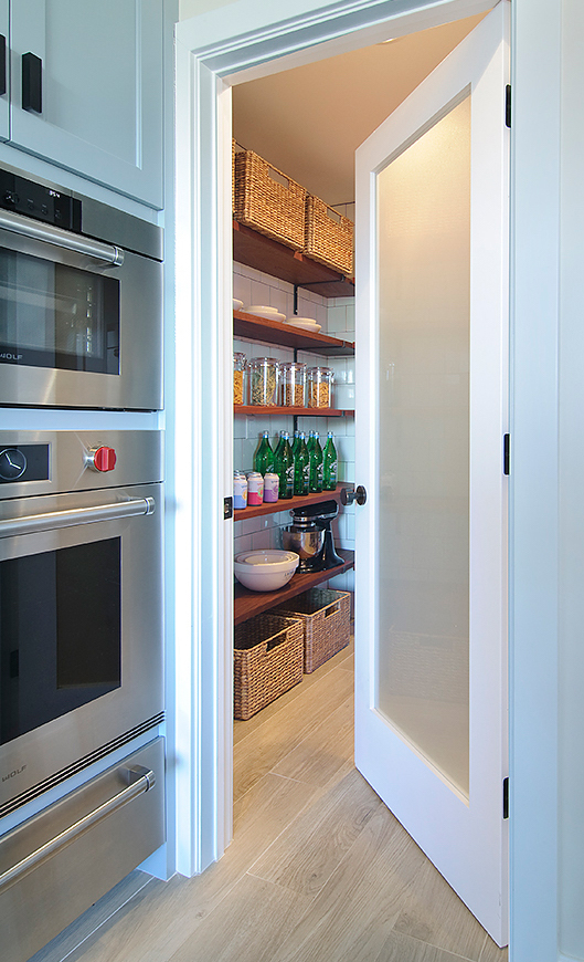 STORAGE ENVY  Floor-to-ceiling square subway tiles connect the kitchen to the pantry while sustainably-forested African Mahogany shelves with custom iron brackets give them storage for days.
