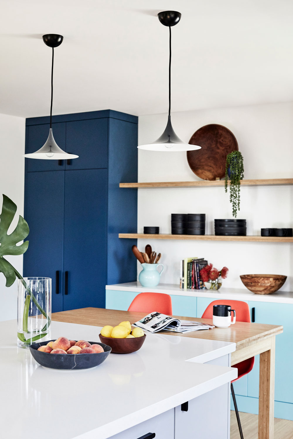 Adding a counter-height bamboo kitchen table to the end of the island makes dinner for the kids so easy. And, those pendant lights makes it feel cozy.